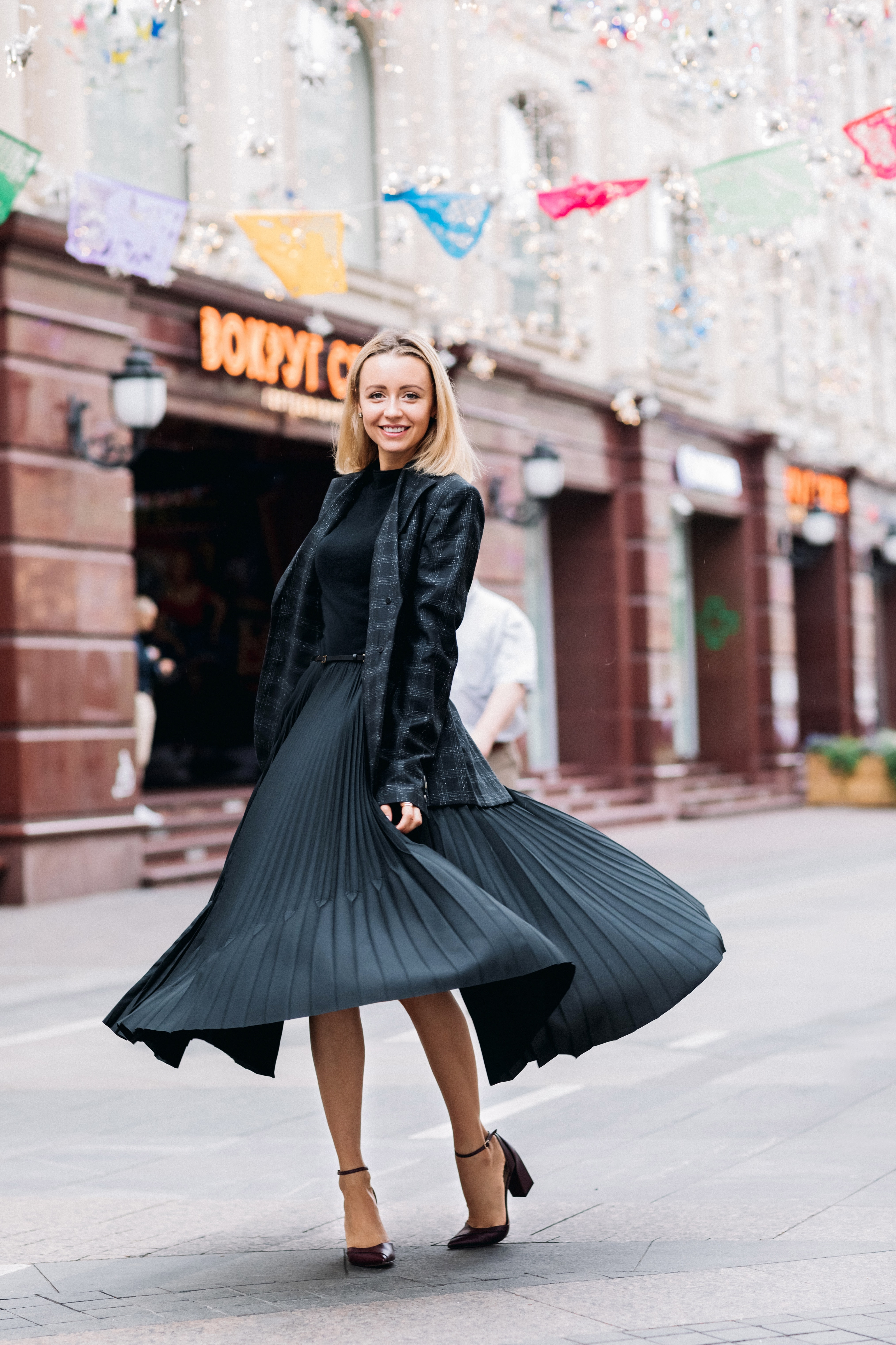 selective focus photo of smiling woman wearing black dress standing on concrete pavement