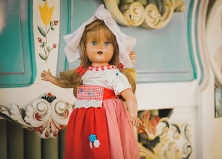 brown haired porcelain doll behind white and blue floral surface