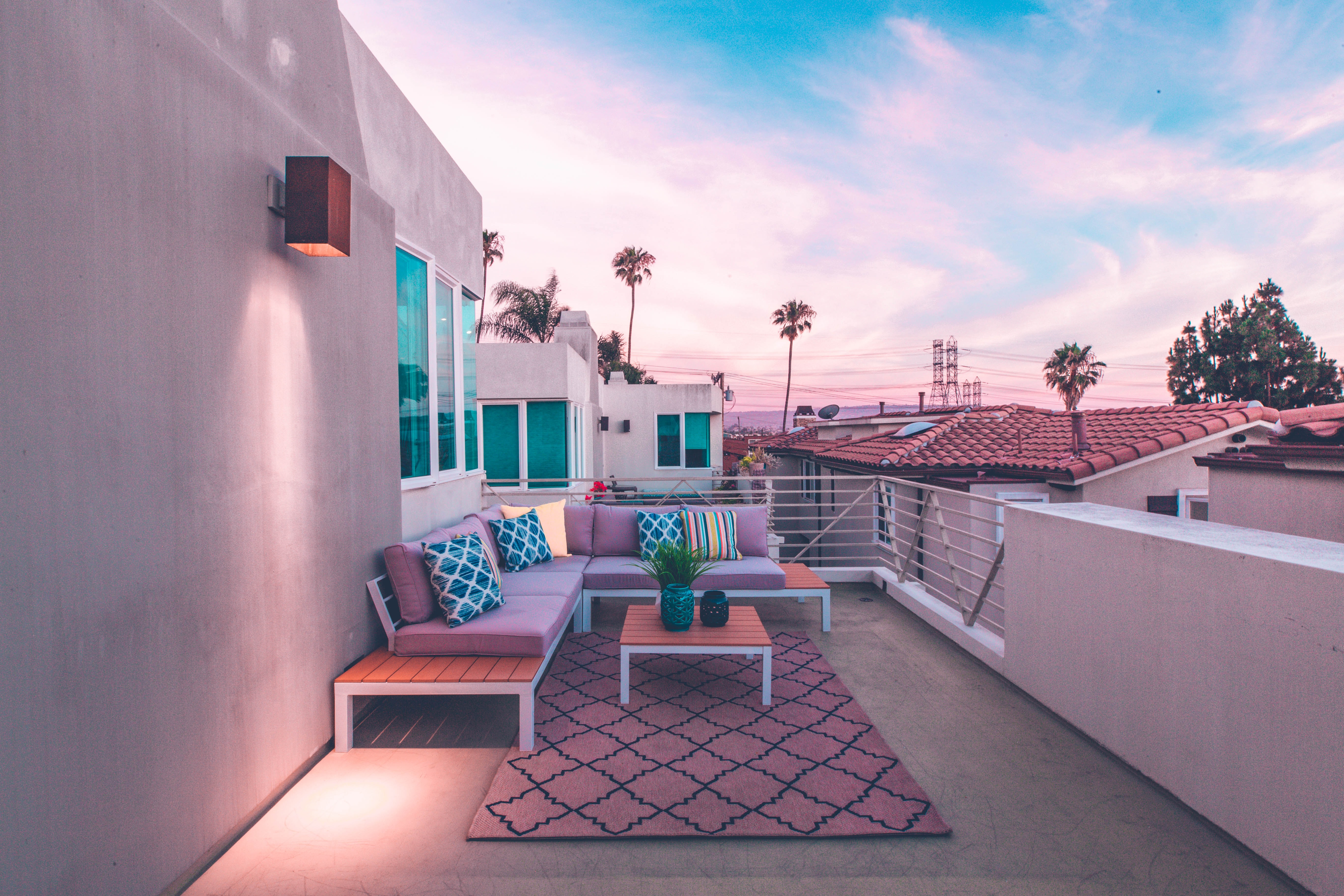 brown wooden sectional bench on top of white concrete house balcony