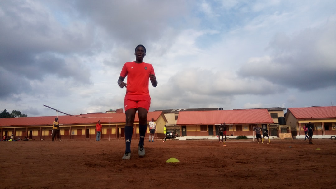 A young boy is seen training to become training on a football pitch. His teammates can be seen at the behind him waiting their turn.  This is what grassroots football looks like in the city of Lagos.