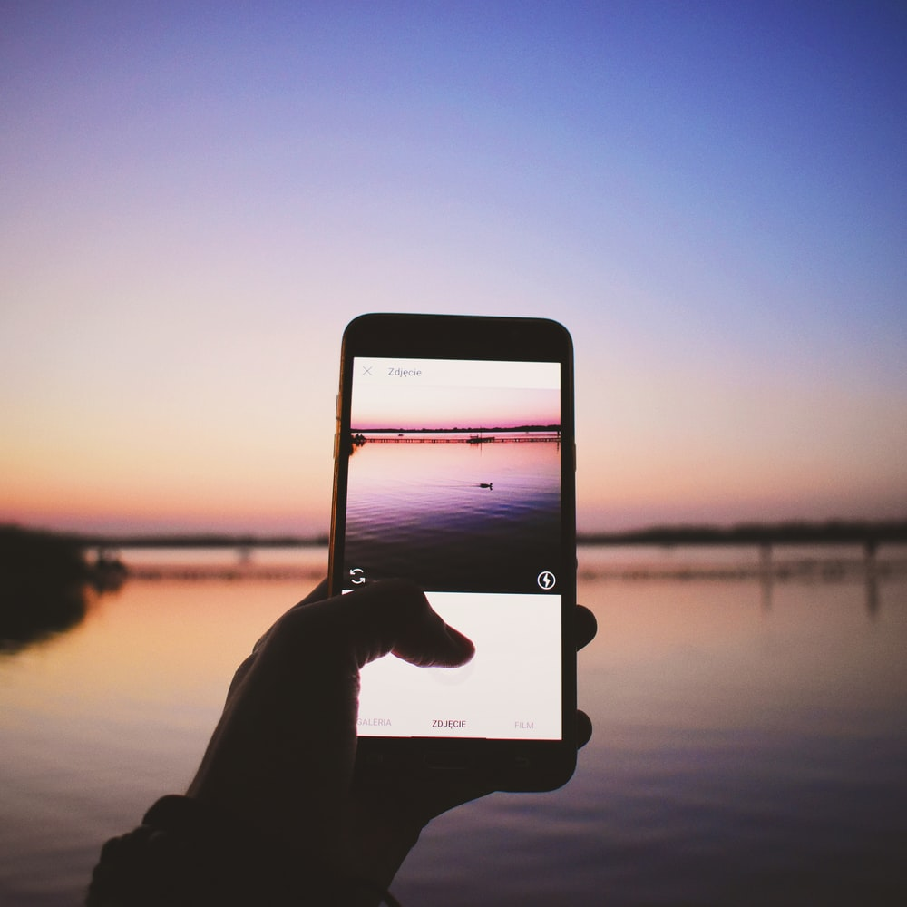 person holding turned-on smartphone taking photo