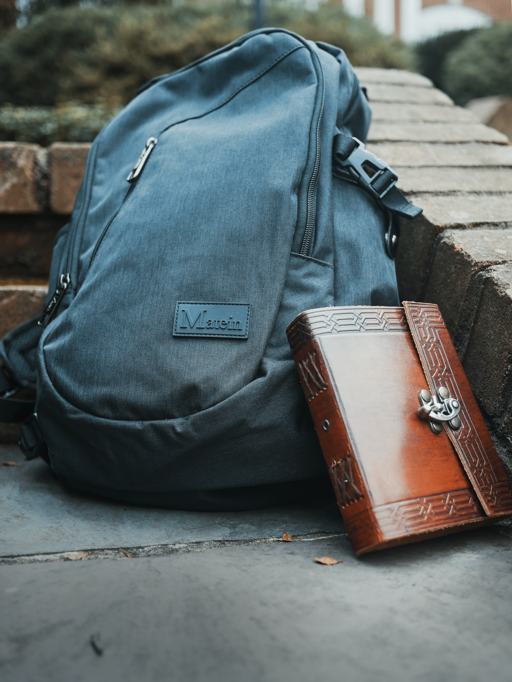 brown leather briefcase and gray Matein bag on concrete slab