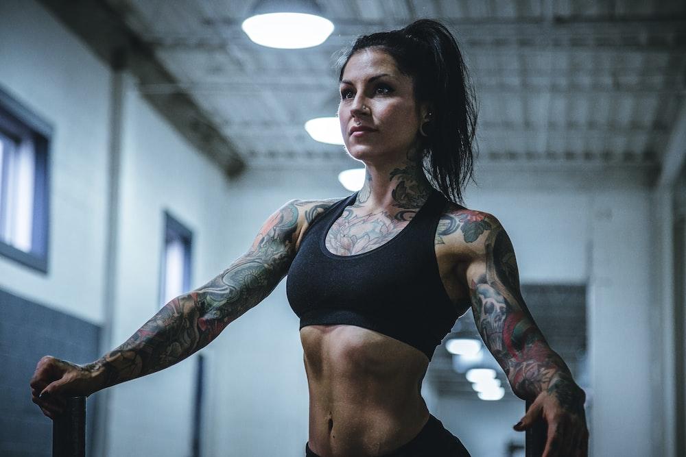 woman wearing black sports bra with tattoos