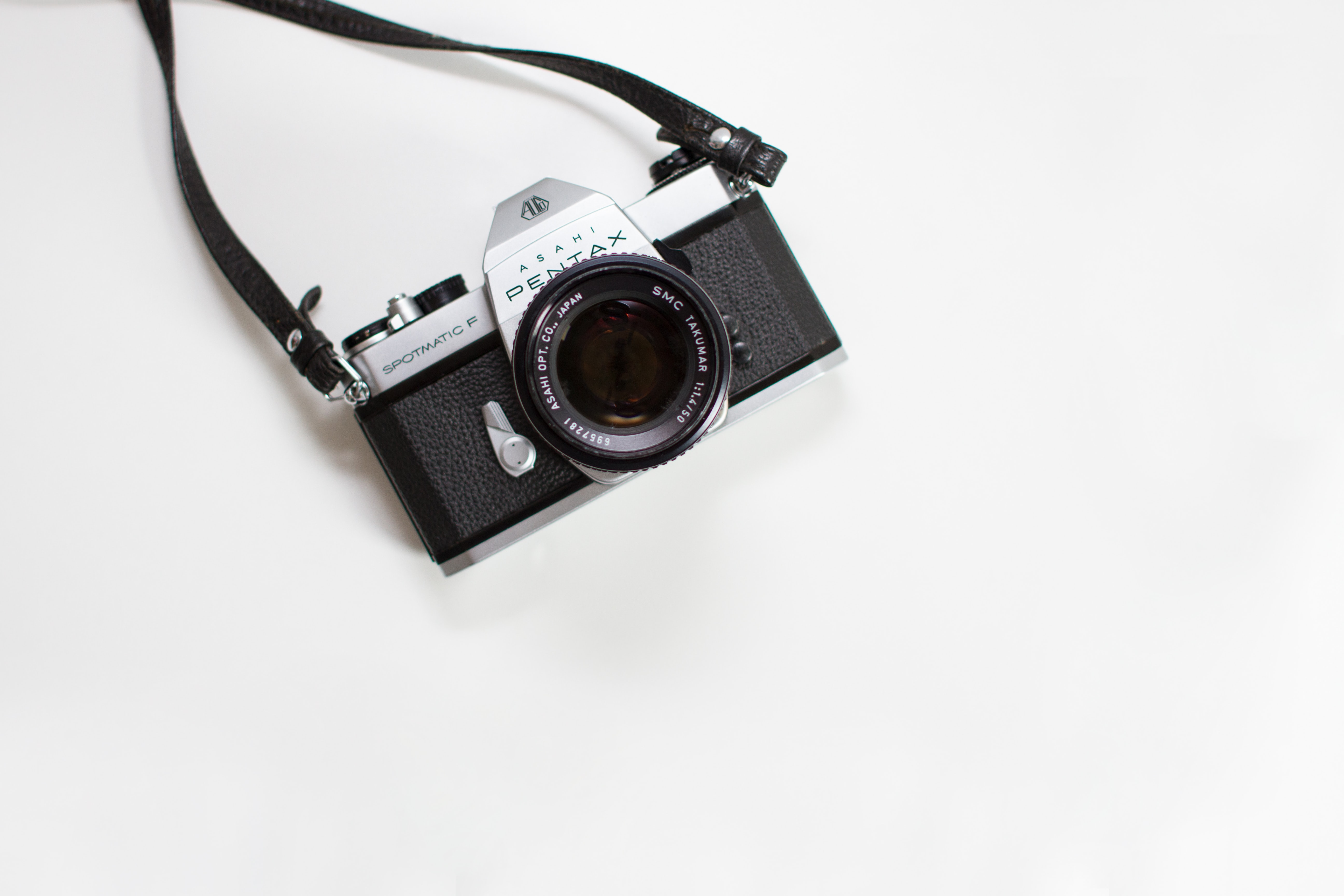 black and gray Pentax digital camera on white surface