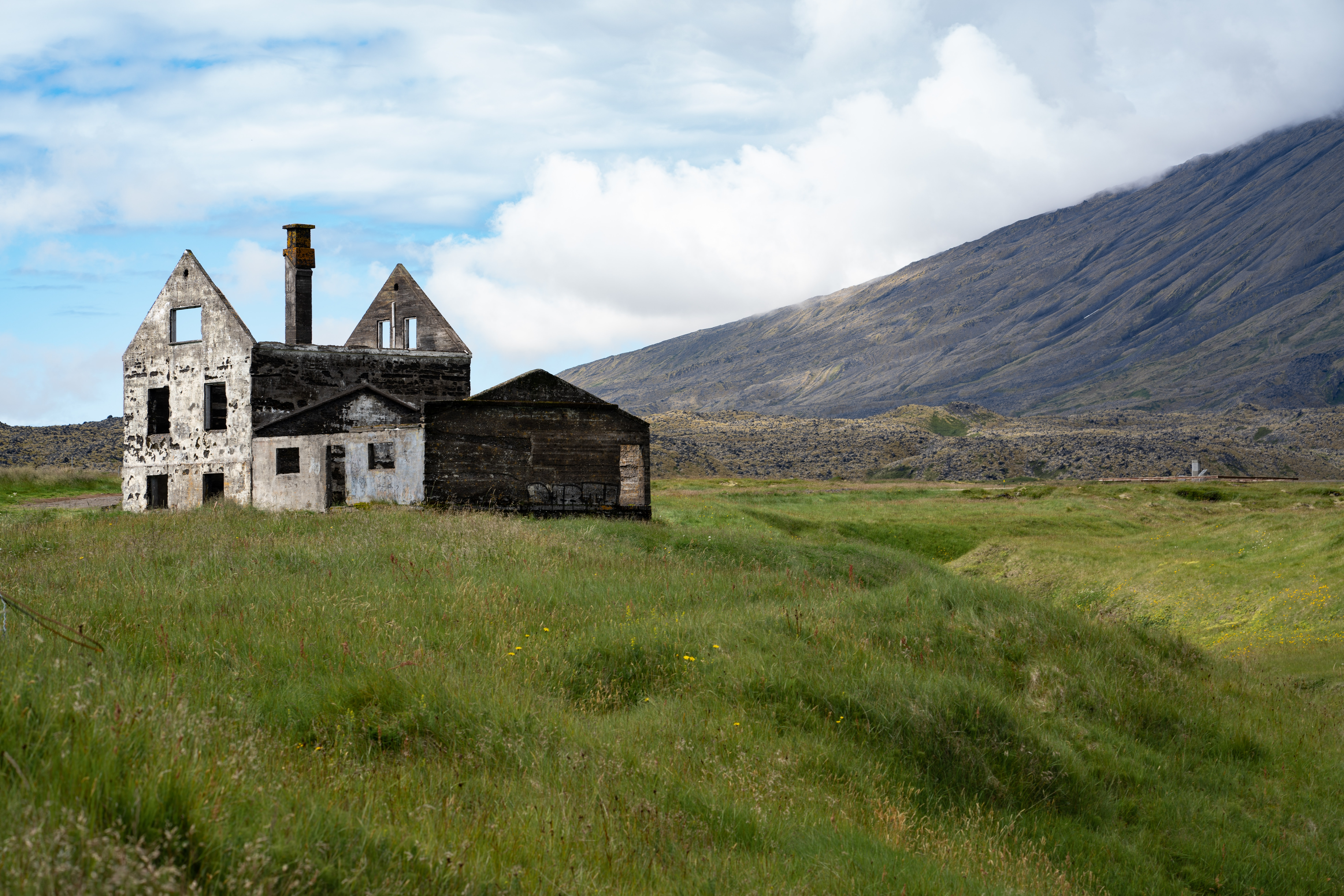 gray building near grass field and mountain under white cloud blue skies