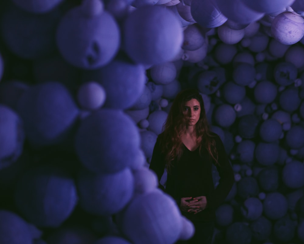woman standing in the middle of piled balls