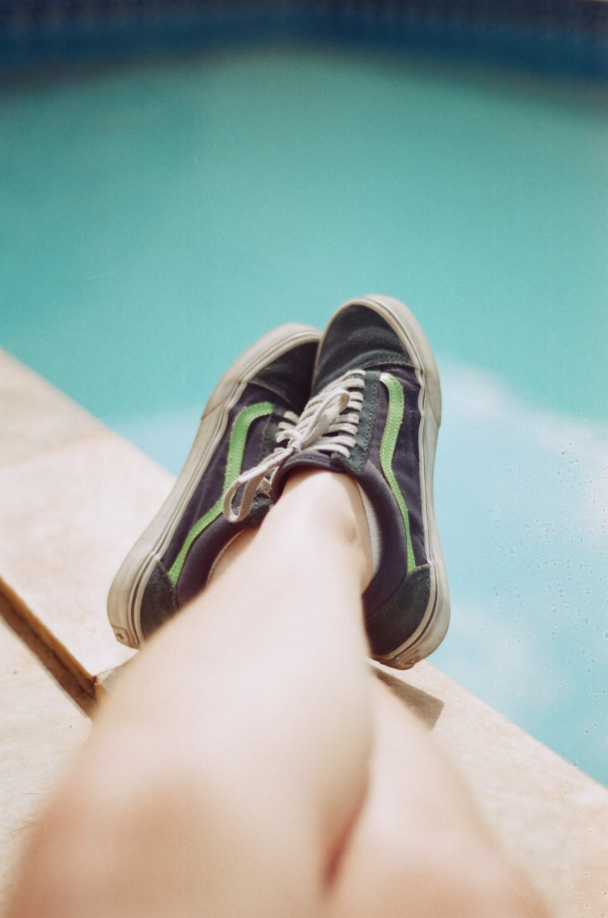 person wearing black-and-green Vans low-top sneakers