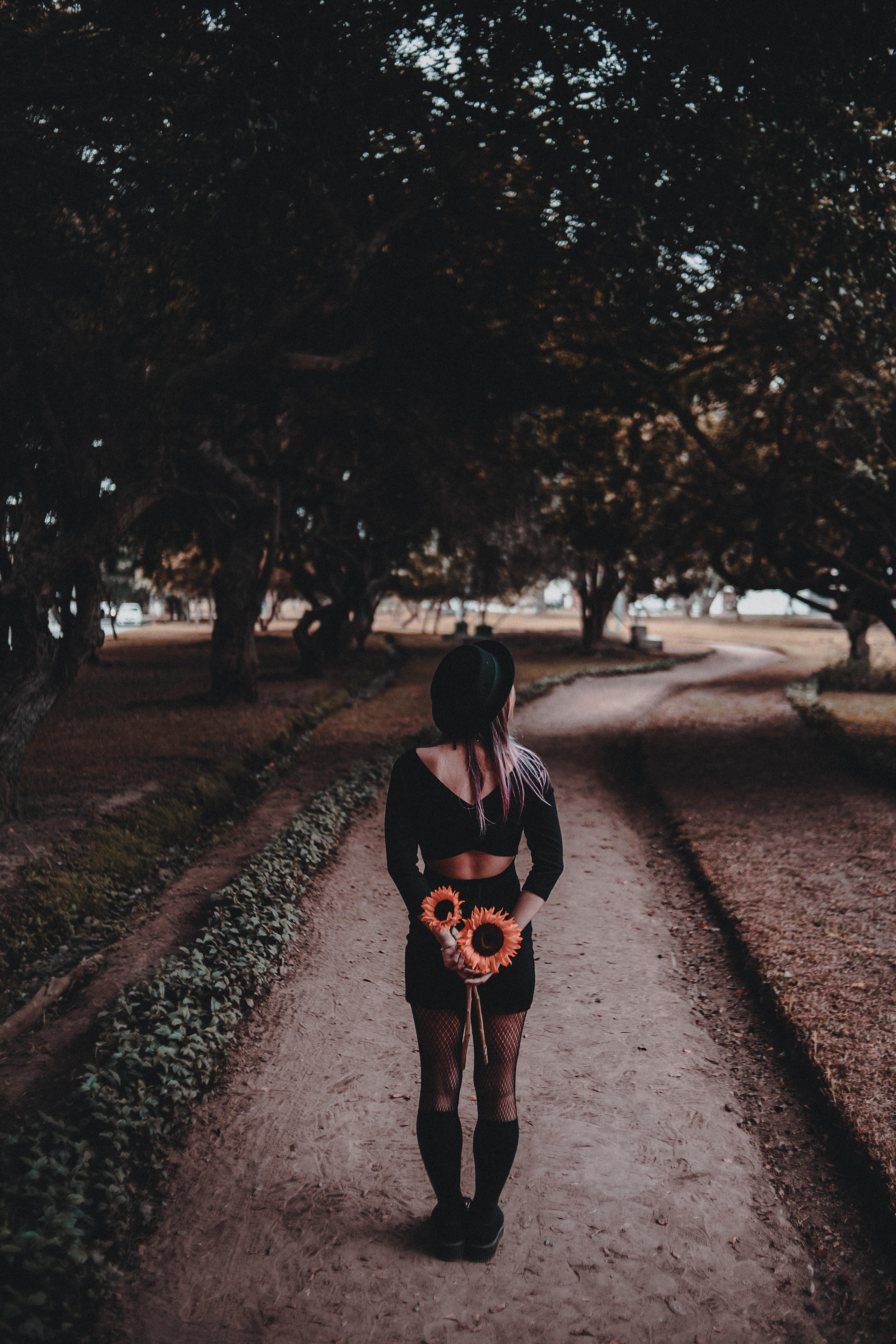 woman walking on park holding flower during daytime