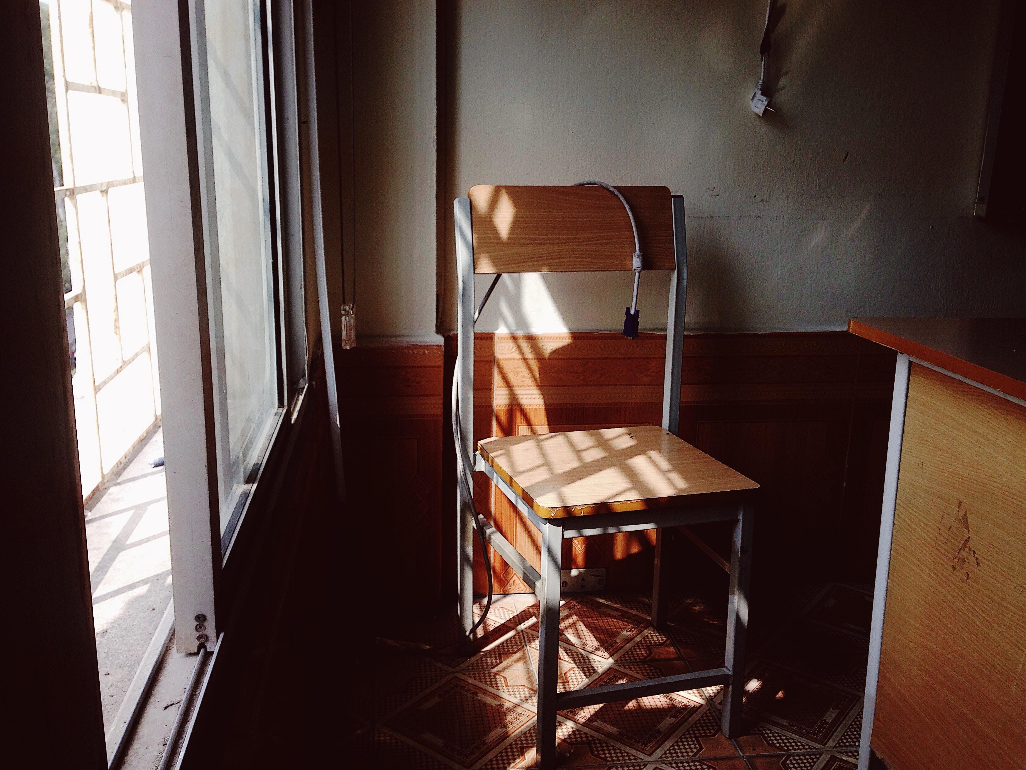 gray and brown chair near window