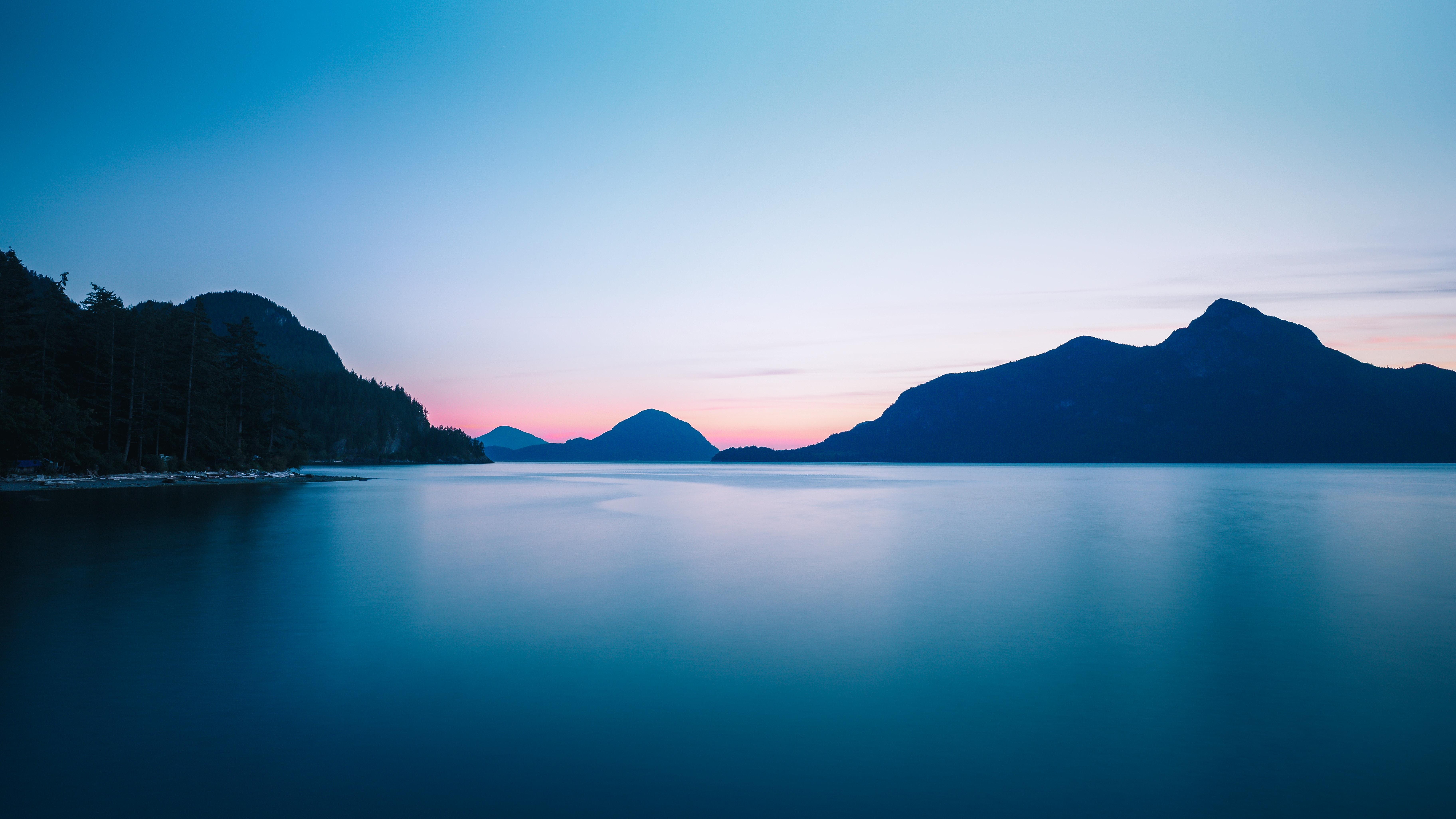 silhouette photo of mountain range near body of water