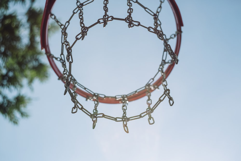 low-angle photo of red basketball hoop under blue sky