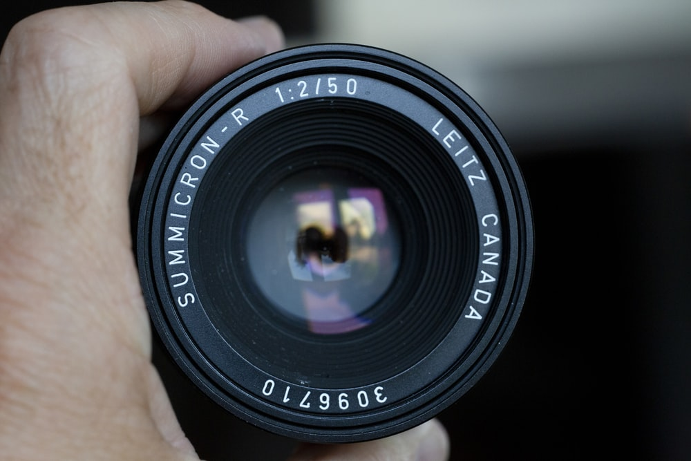 person holding black Summicron-R camera lens