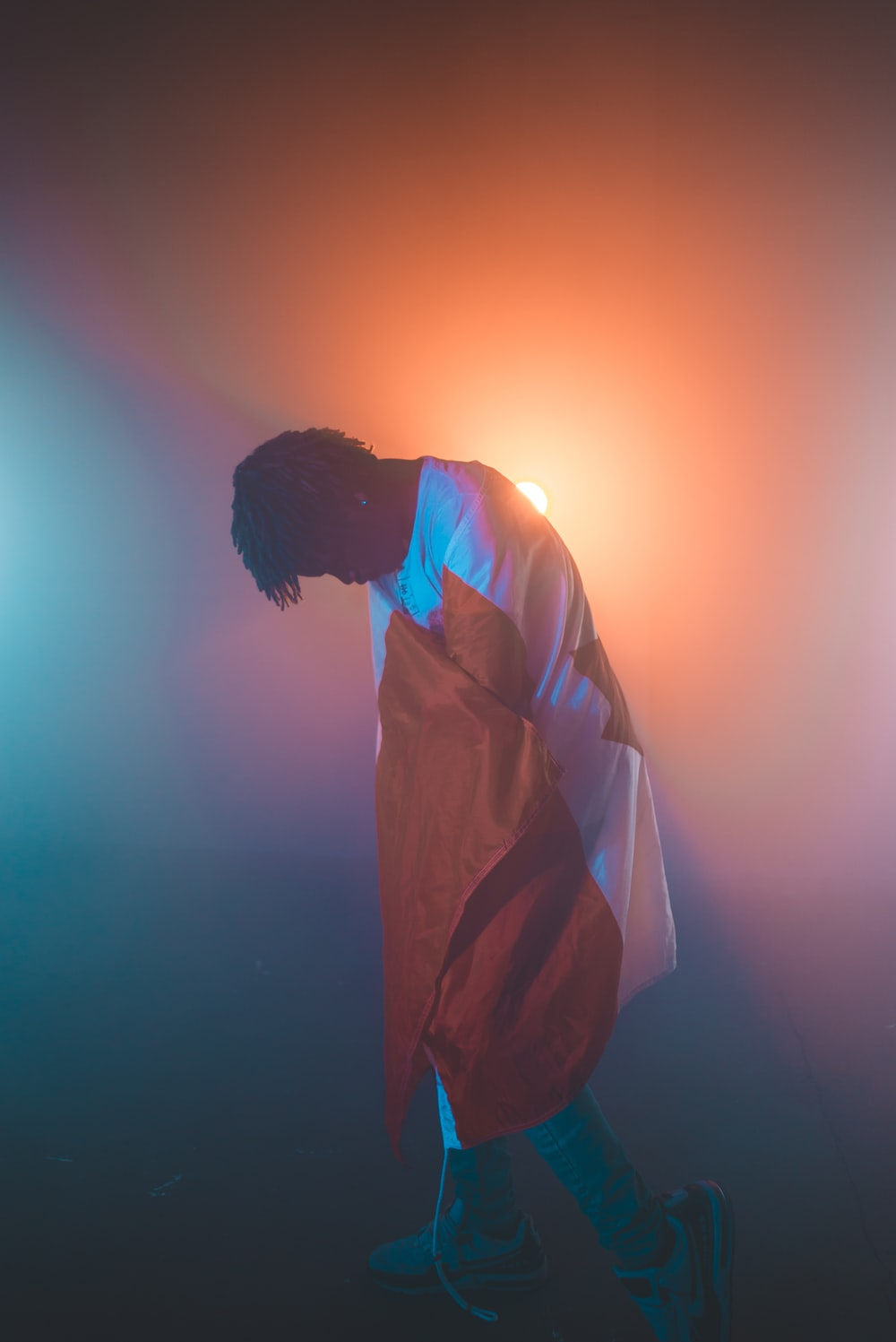 man wearing white and orange long-sleeved shirt standing near orange light