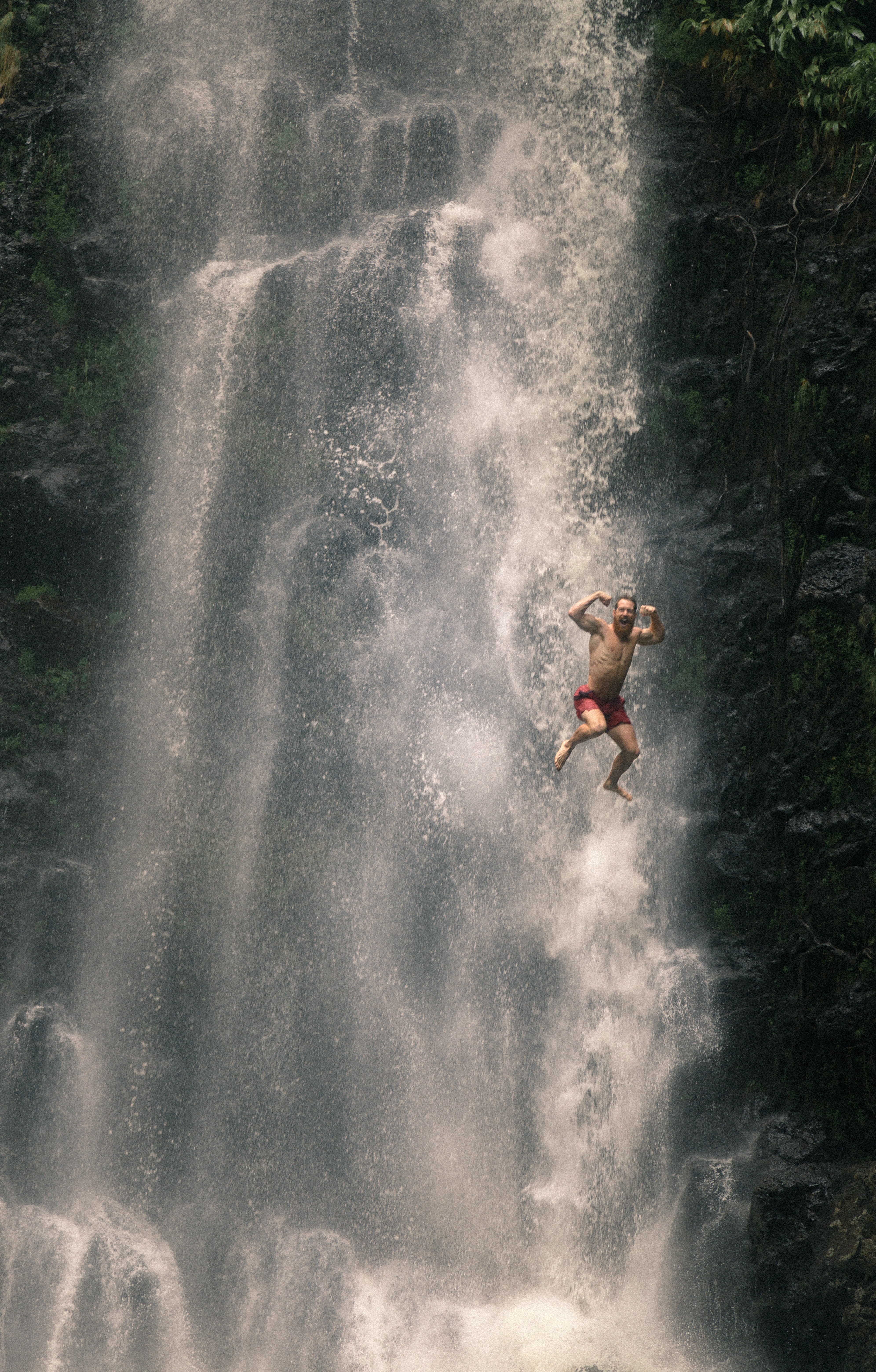 man in red shorts jumping along water