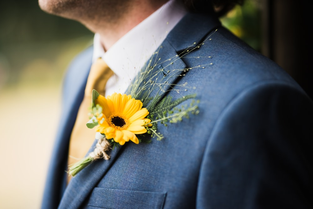 man in blue suit jacket with yellow clipped flower