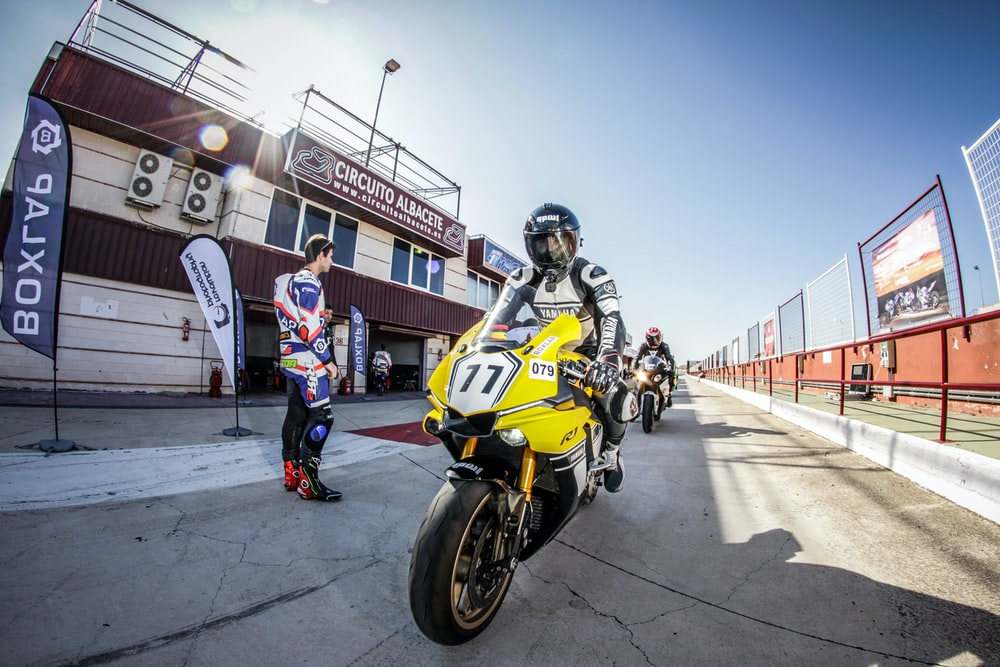 man riding on yellow motorcycle