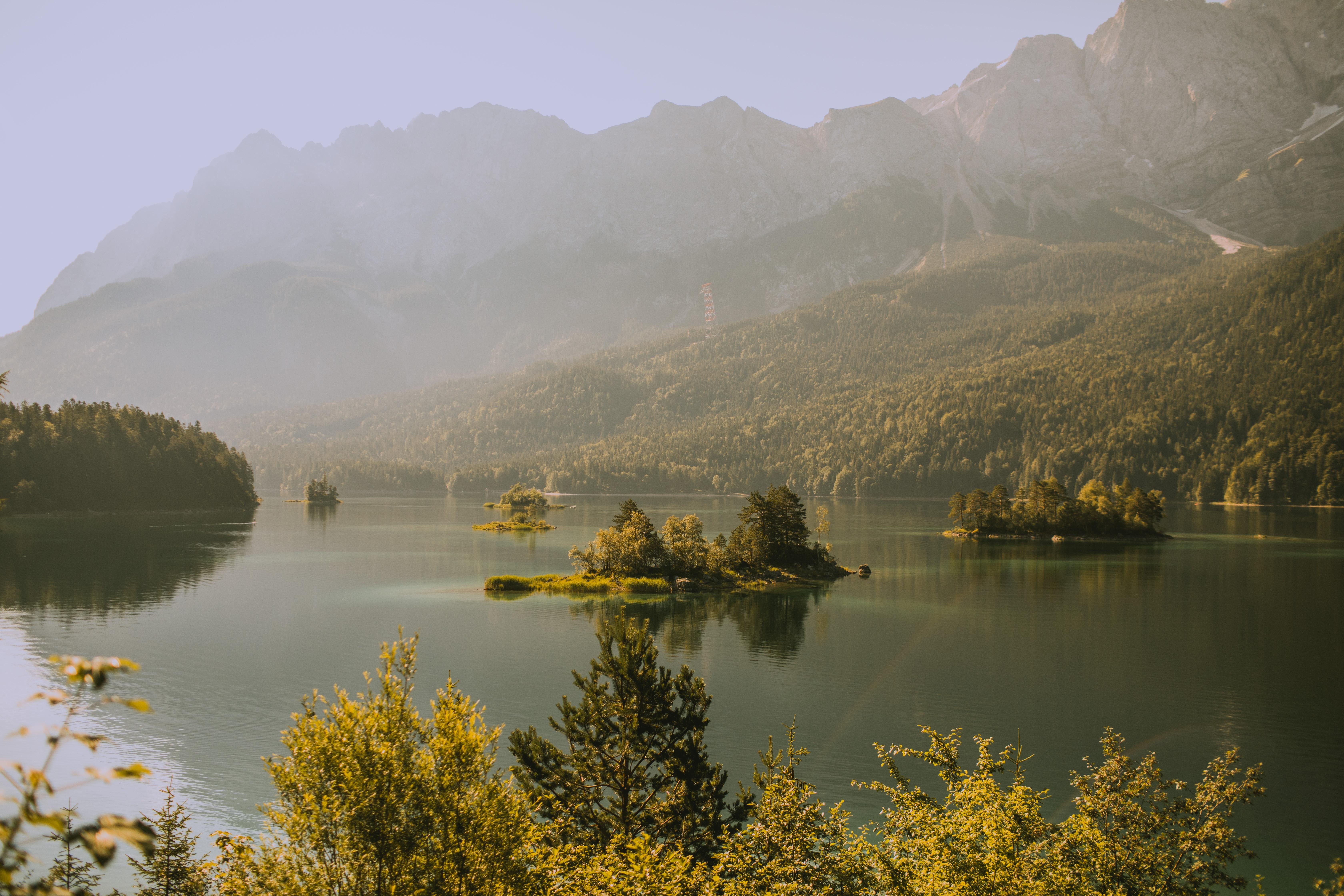 body of water within mountain range during fog