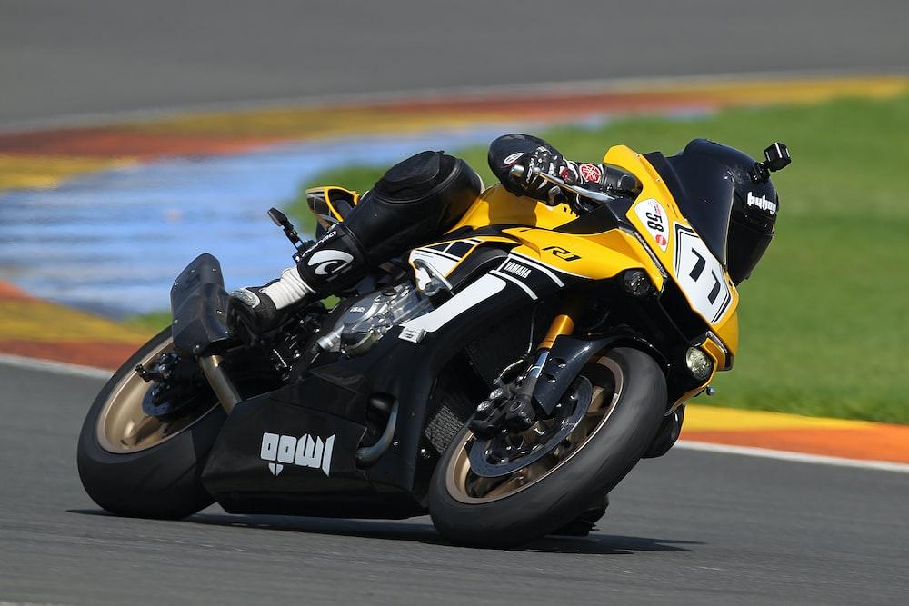 man riding on yellow and black sports bike