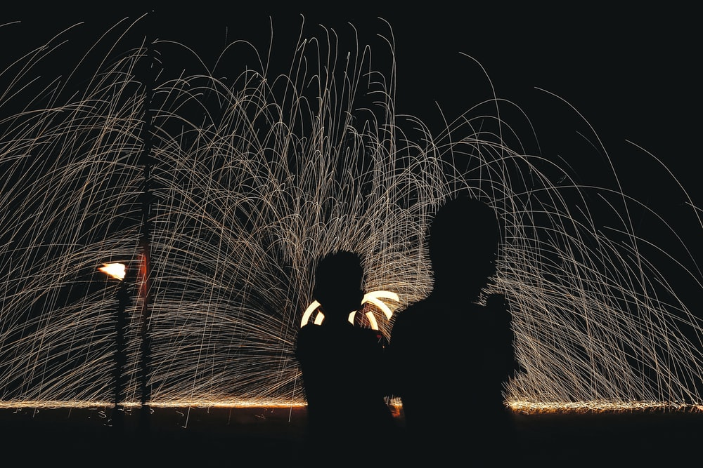 man and woman kissing in front of fireworks display during night time