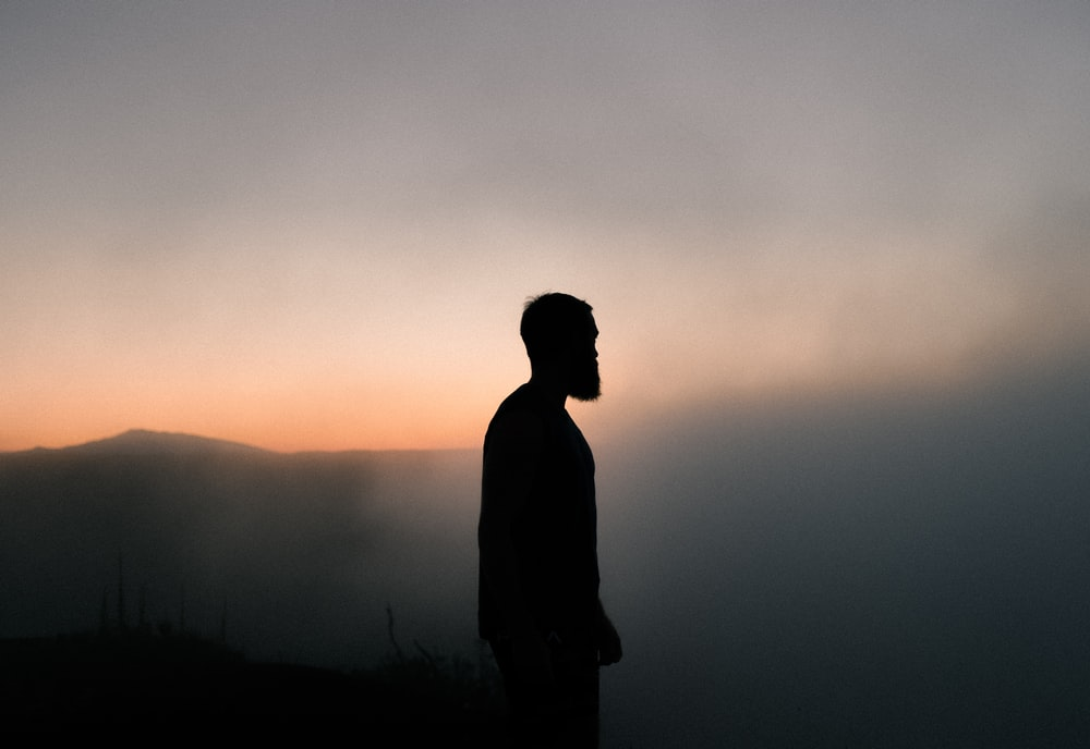 silhouette of man surrounded with fog during golden hour