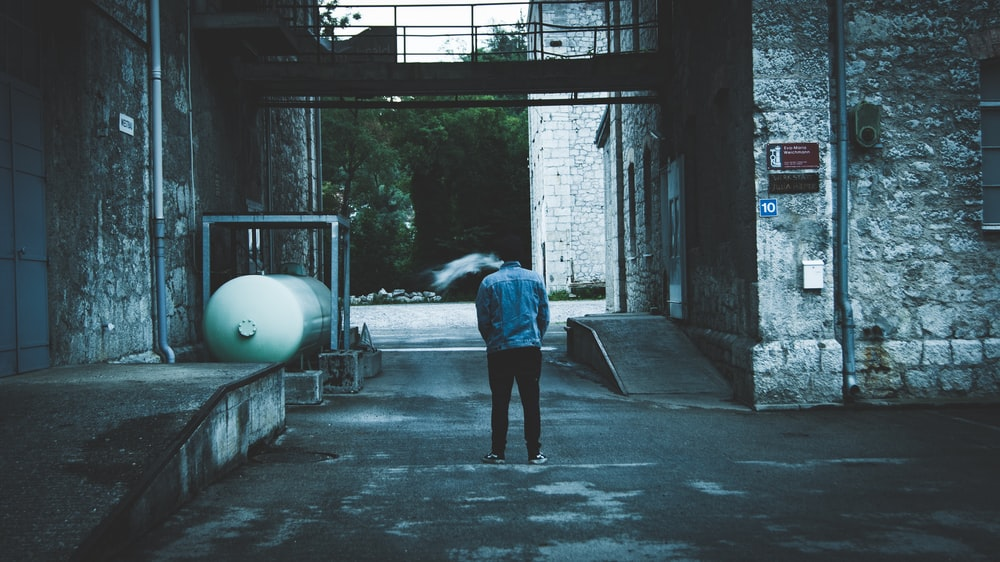 person walking on hallway near tank