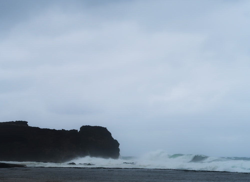 white seawaves near silhouette rock formation under white cloudy sky at daytime