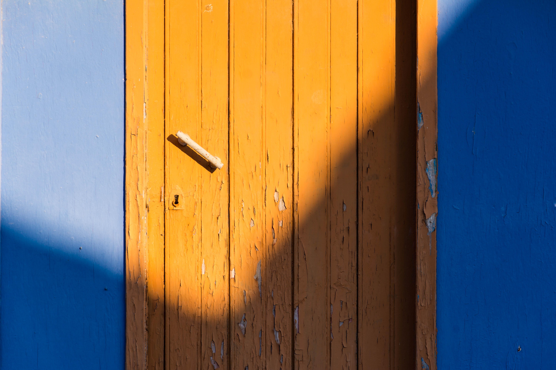 brown wooden door beside blue wall