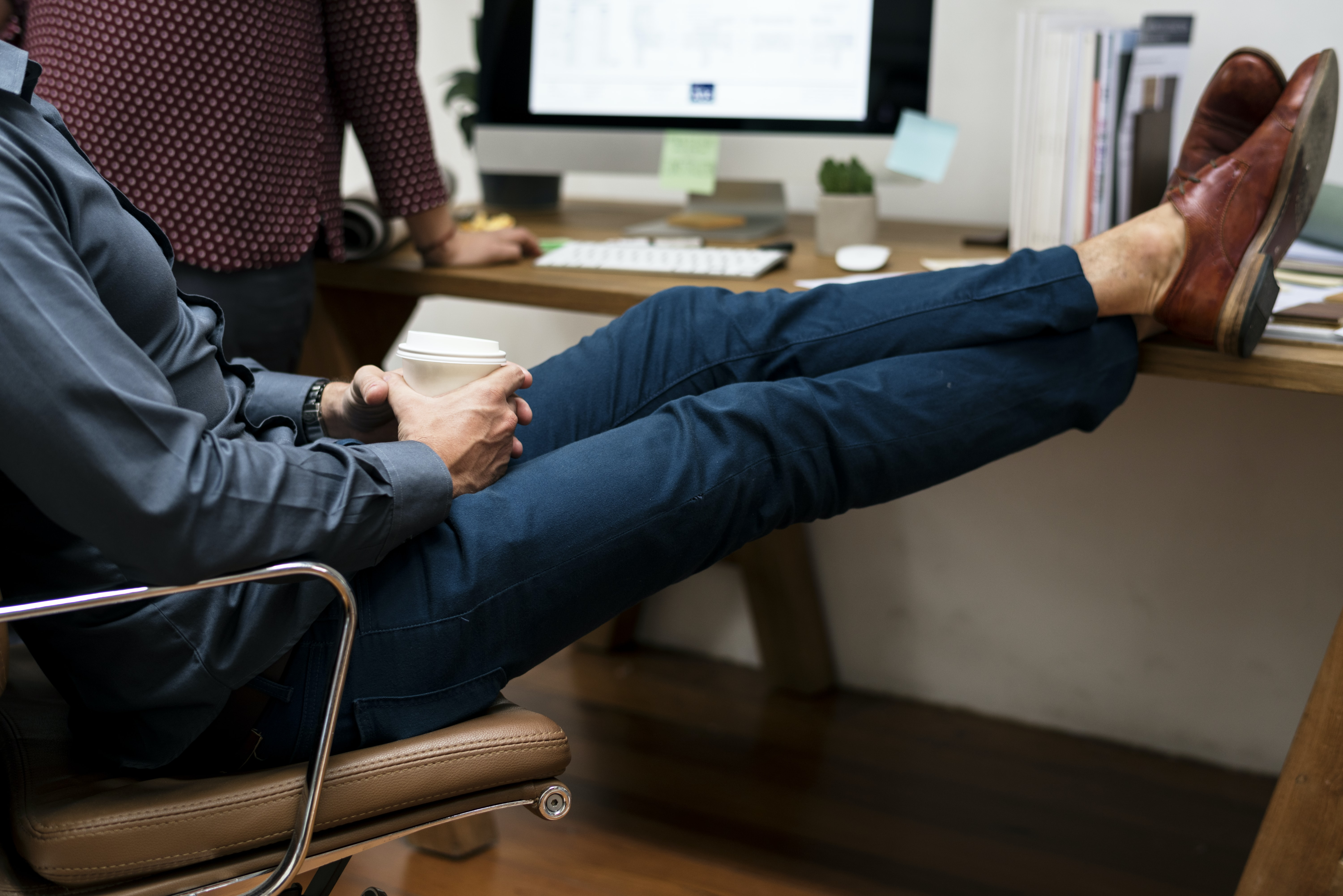person sitting on chair cross leg on table
