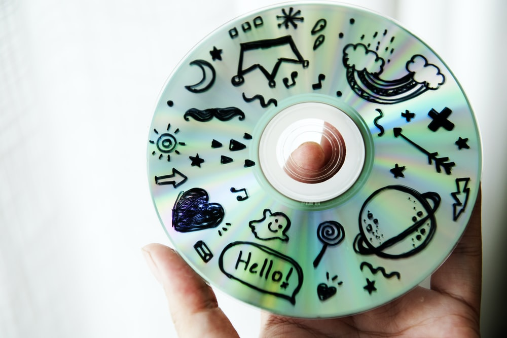 person holding disc with doodles