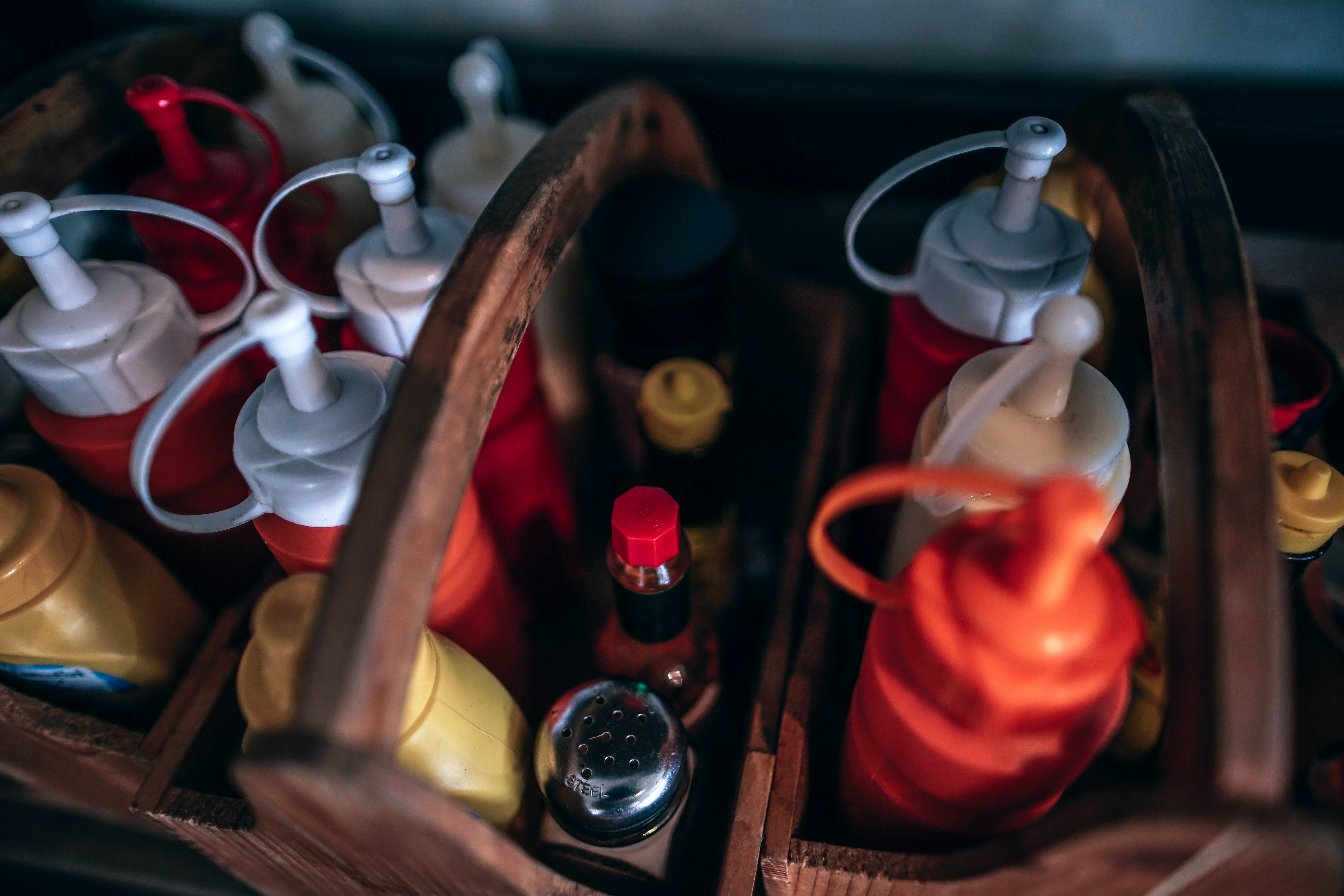 depth of field photography of condiment and sauce bottles in organizer