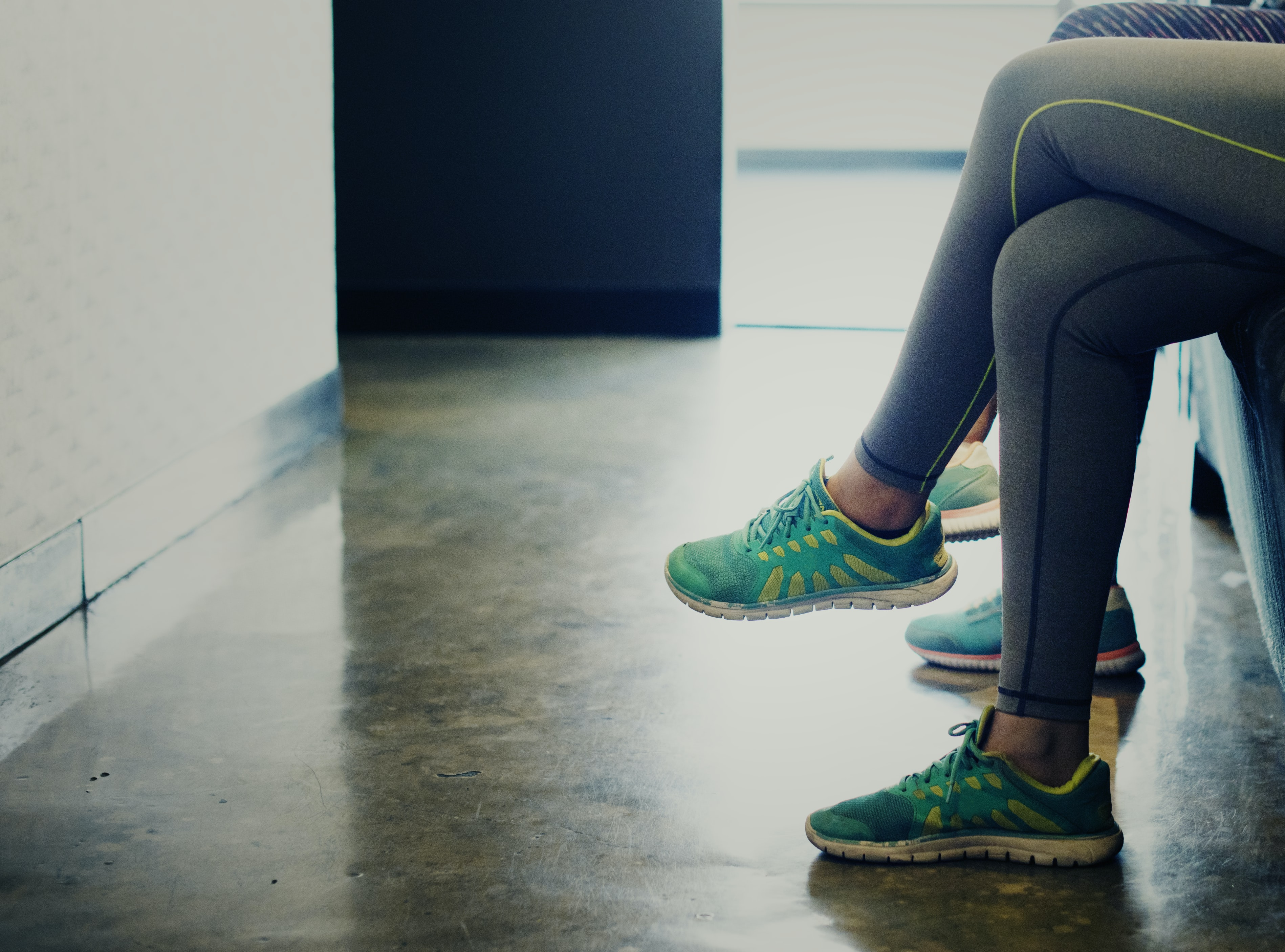 woman wearing pair of green running shoes