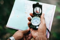 selective focus photo of person holding compass