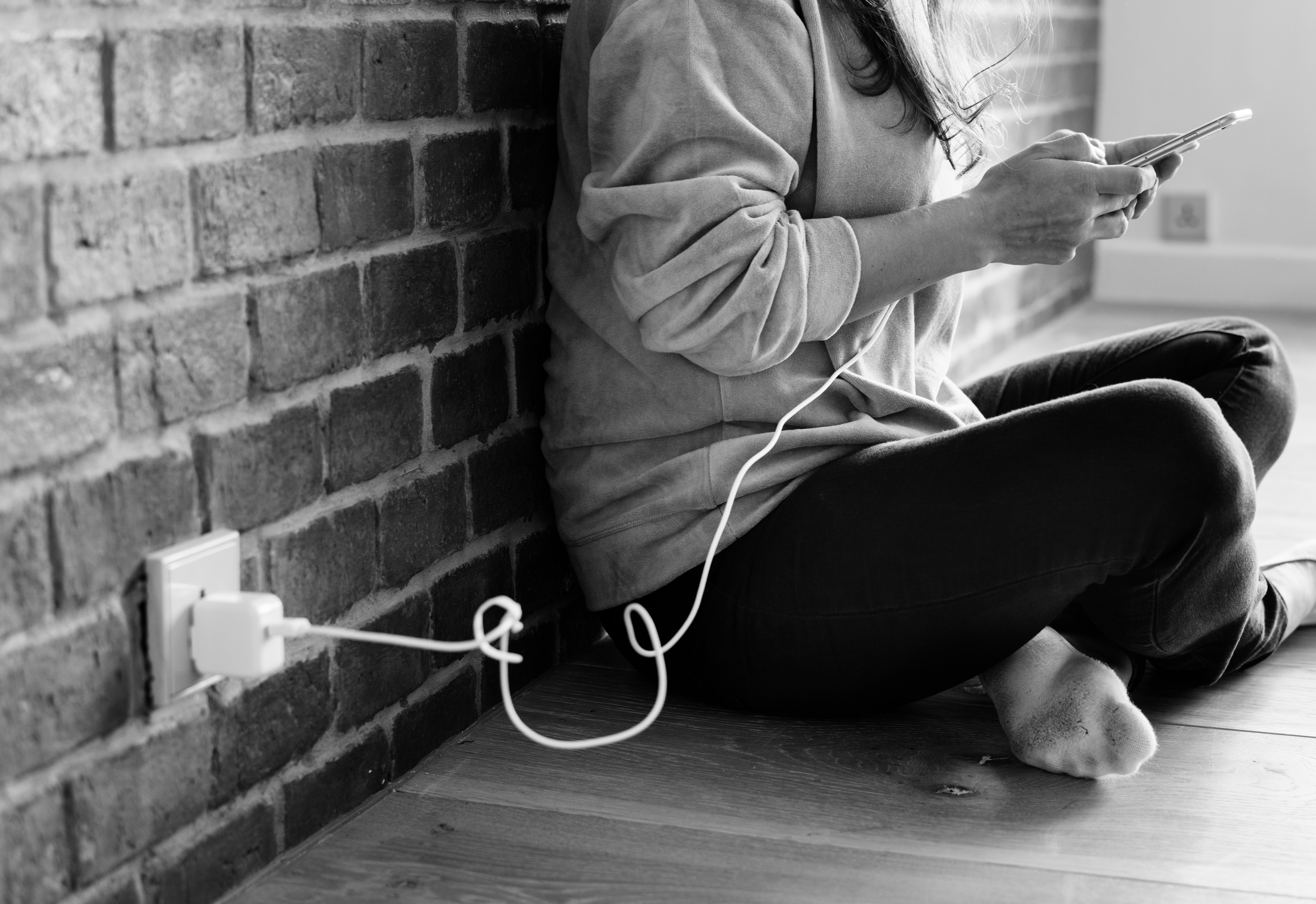 grayscale photo of person sitting beside wall using smartphone