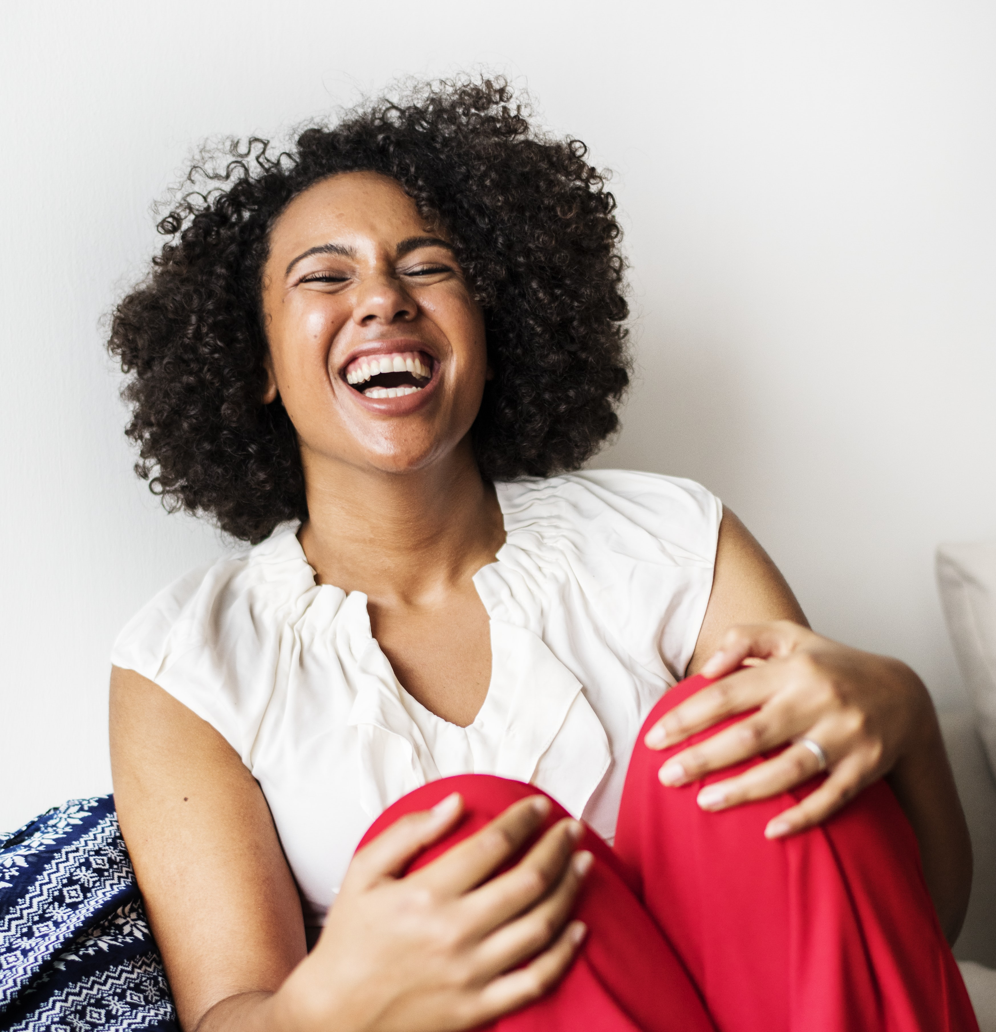 woman holding her knees while smiling