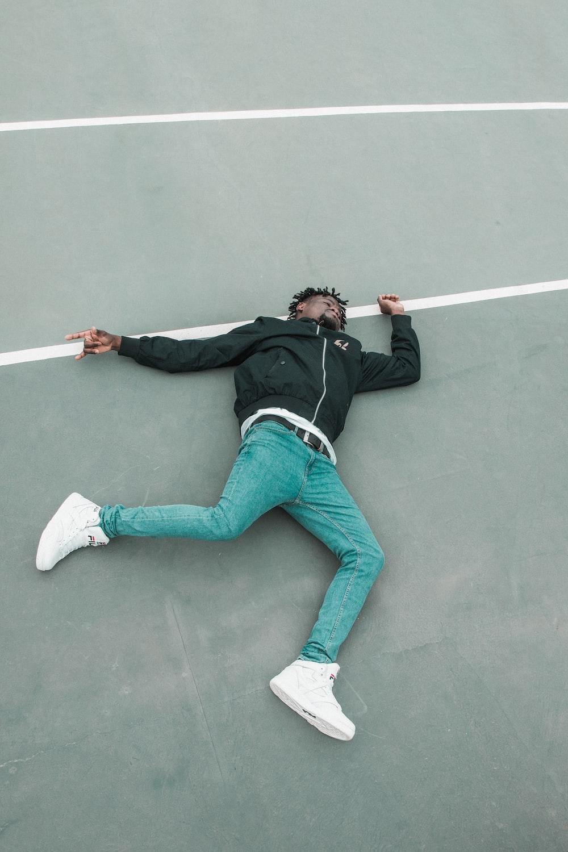 man lying on gray white lined concrete floor