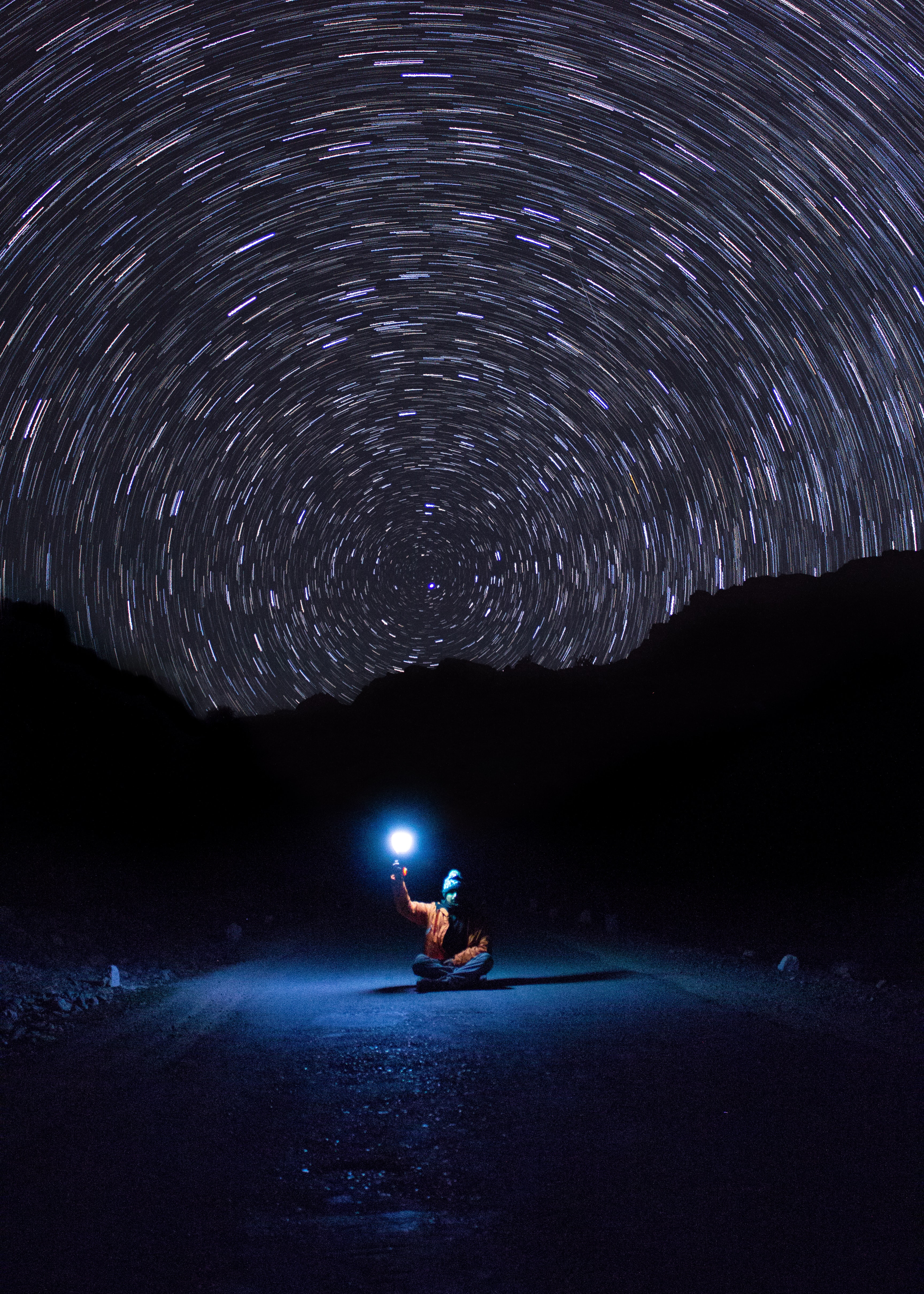 photo of person sitting on pave road holding light
