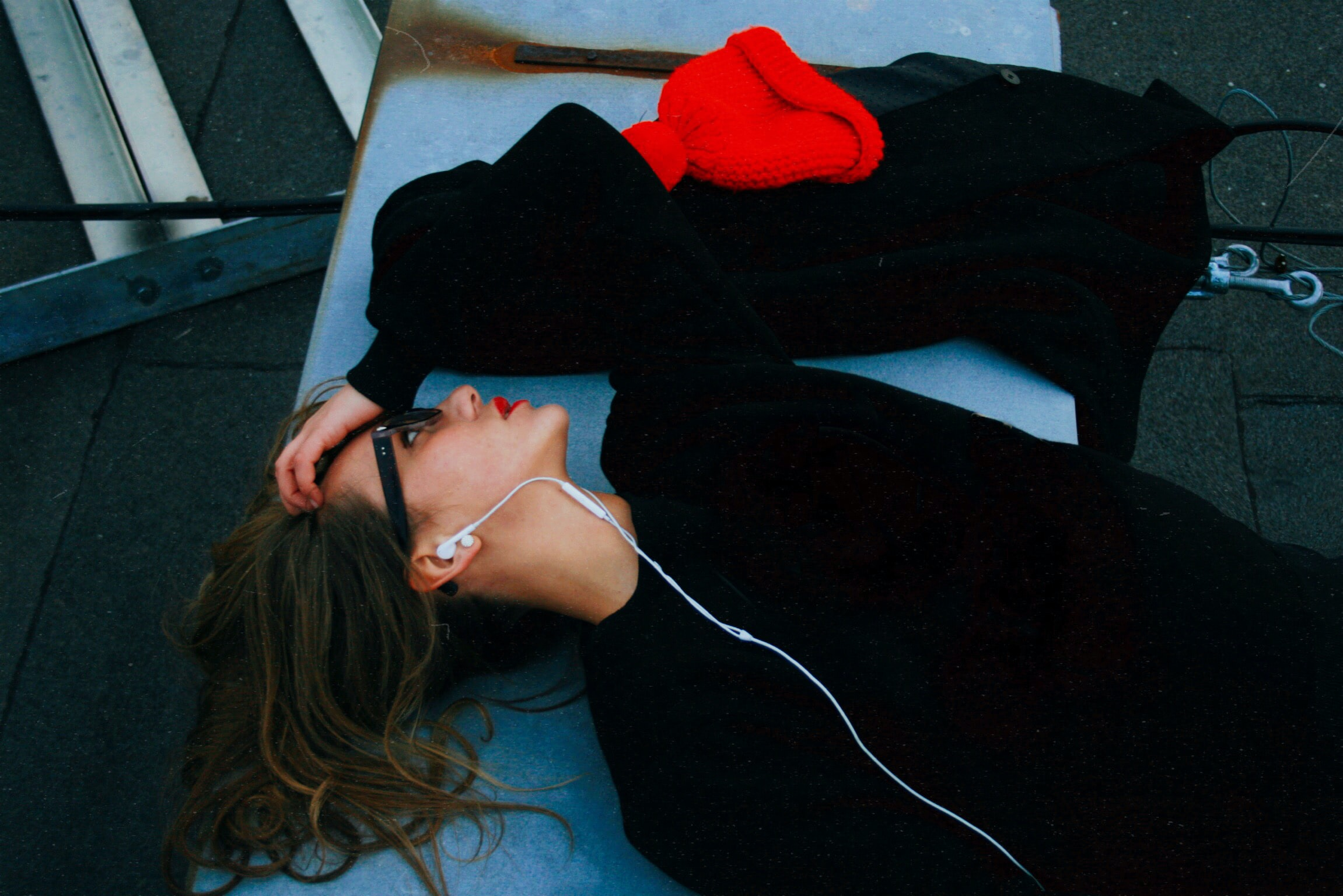 woman in black shirt lying on blue surface