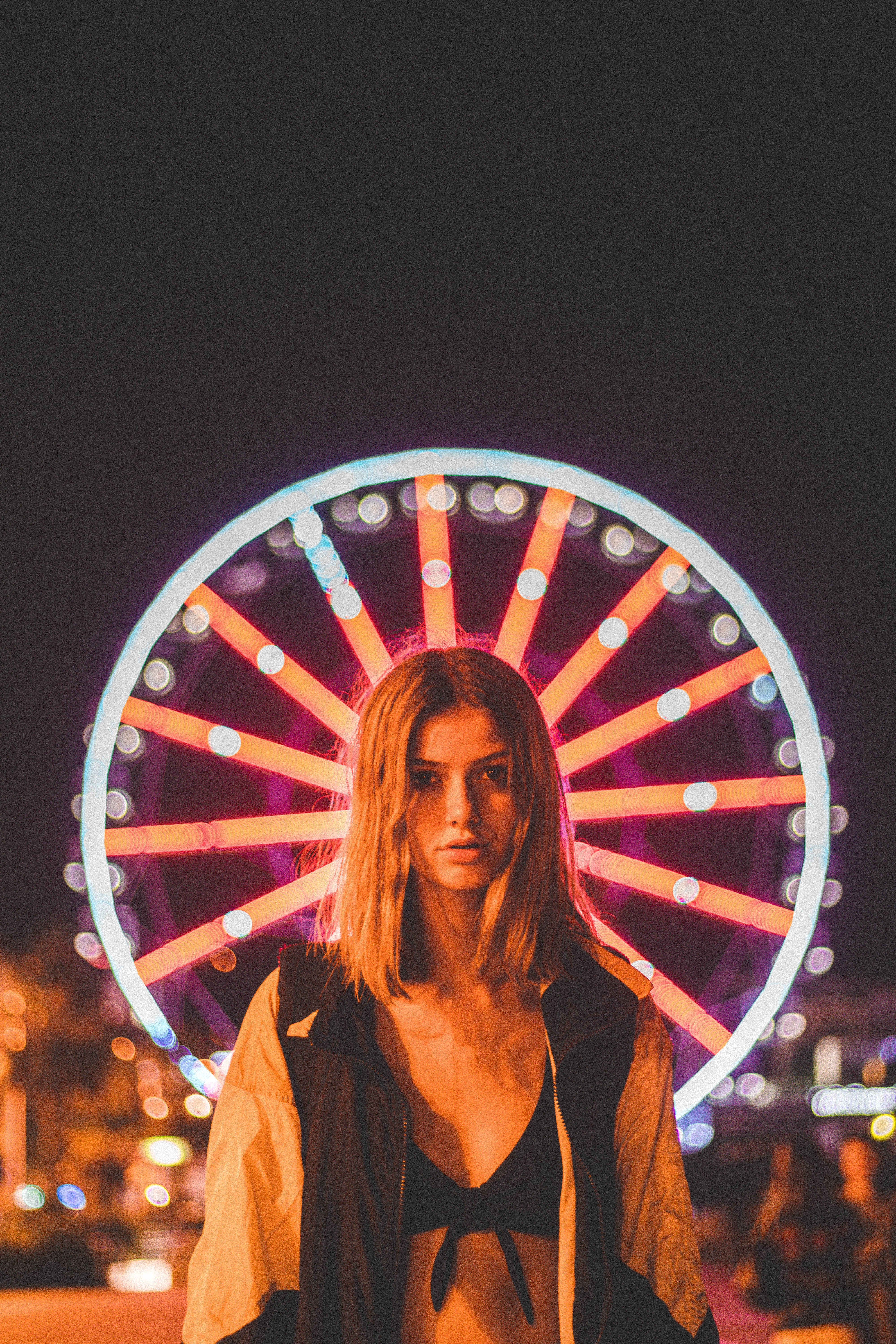 woman standing in front of lighted Ferris wheel at nighttime