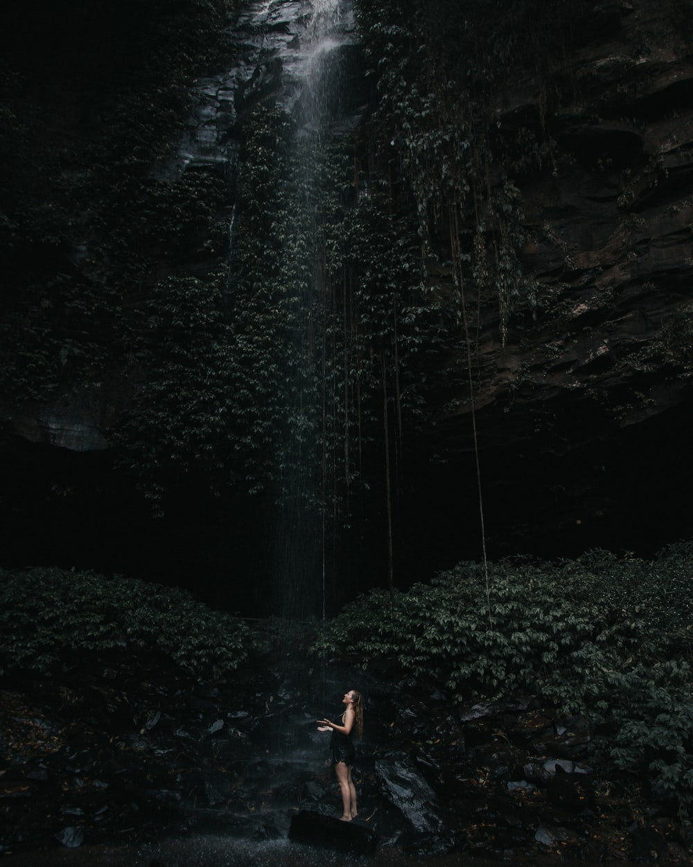 woman standing under waterfalls during daytime