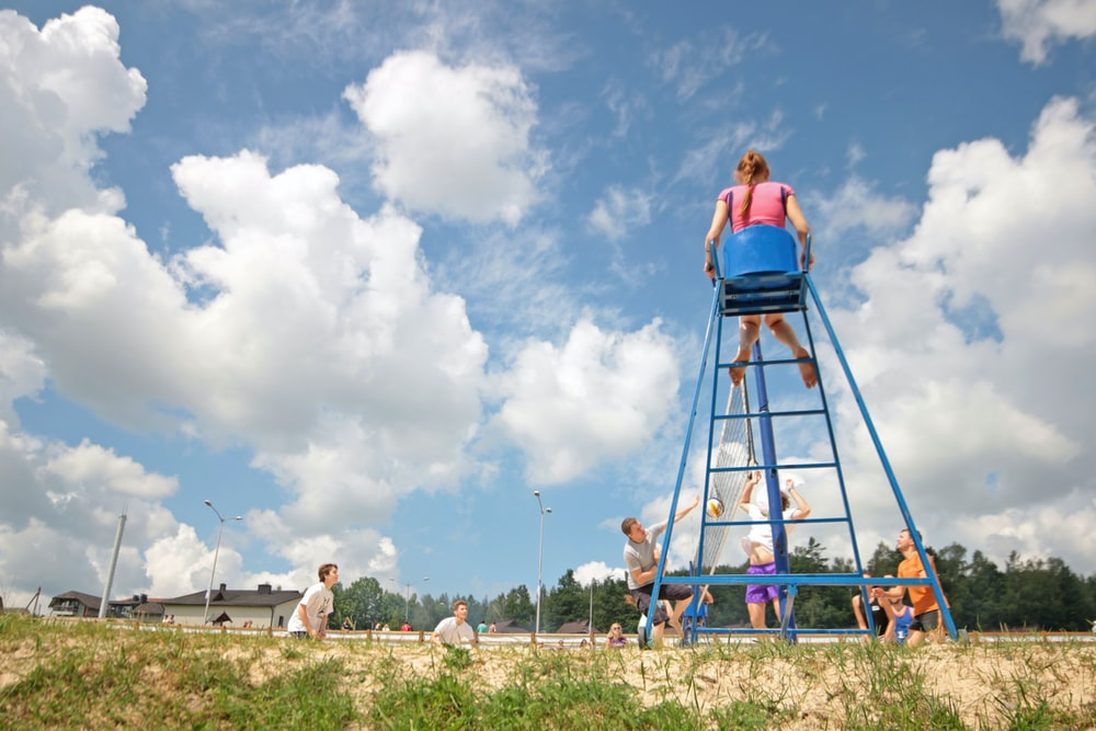 group of teens playing volleyball girl sitting on umpire's chair