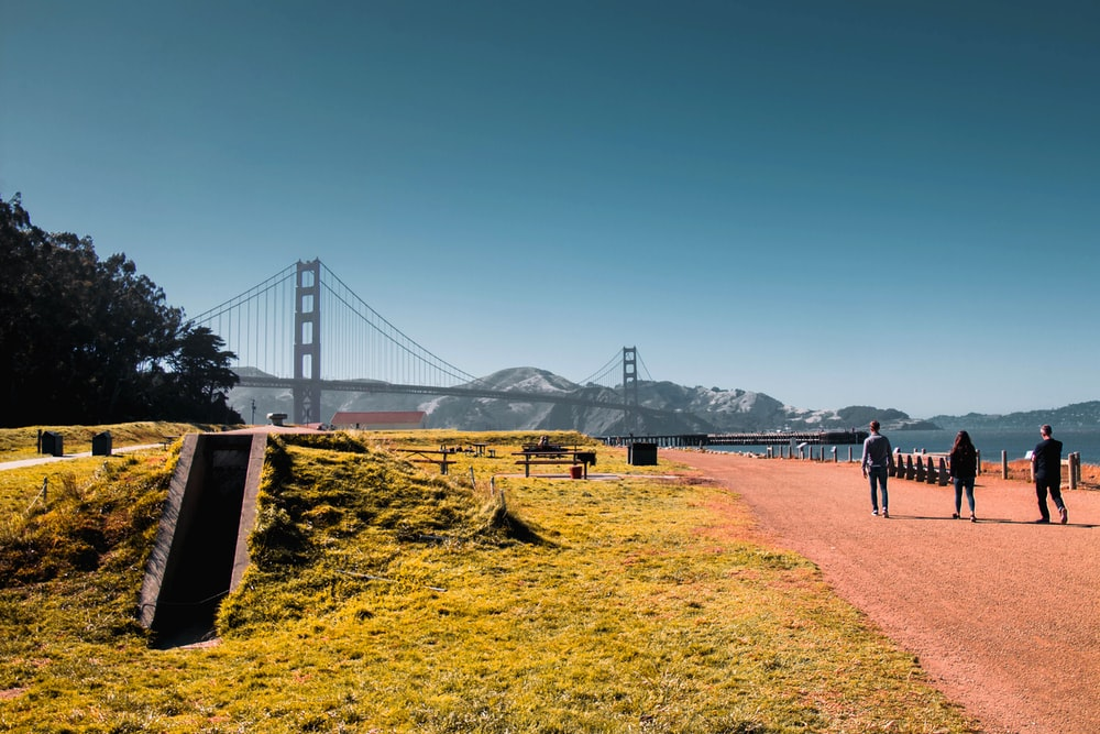 mens and woman walking near bridge and mountain at daytime