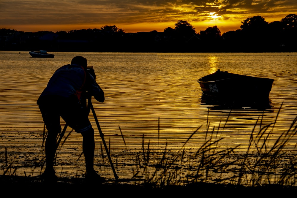 silhouette photography of a man taking picture on boat