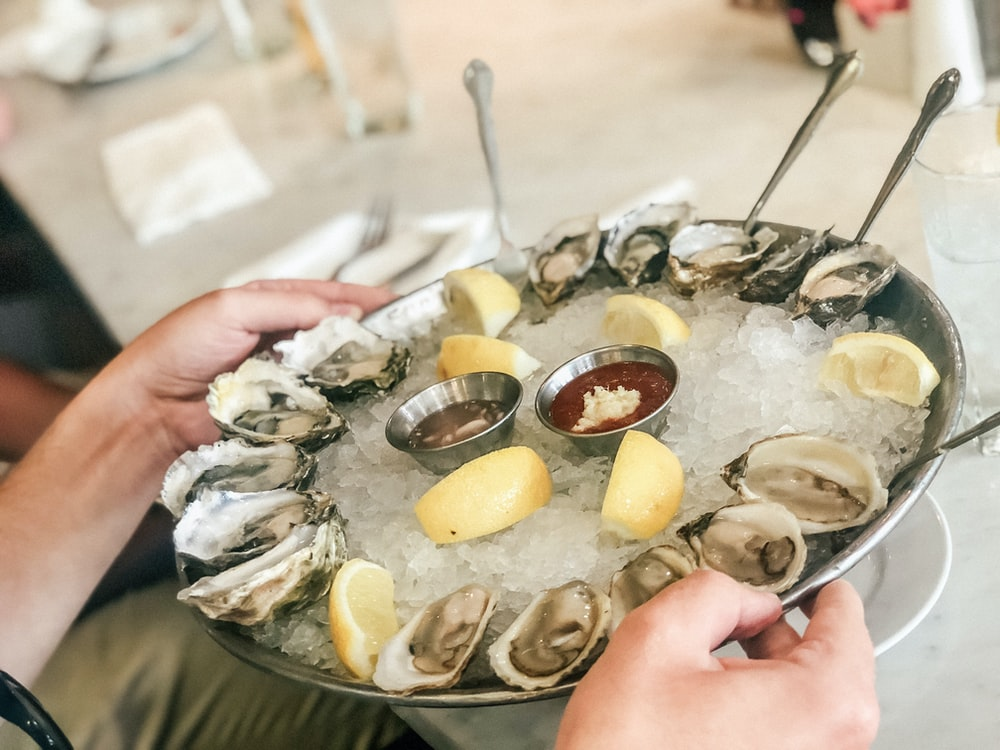 person holding plate with oysters