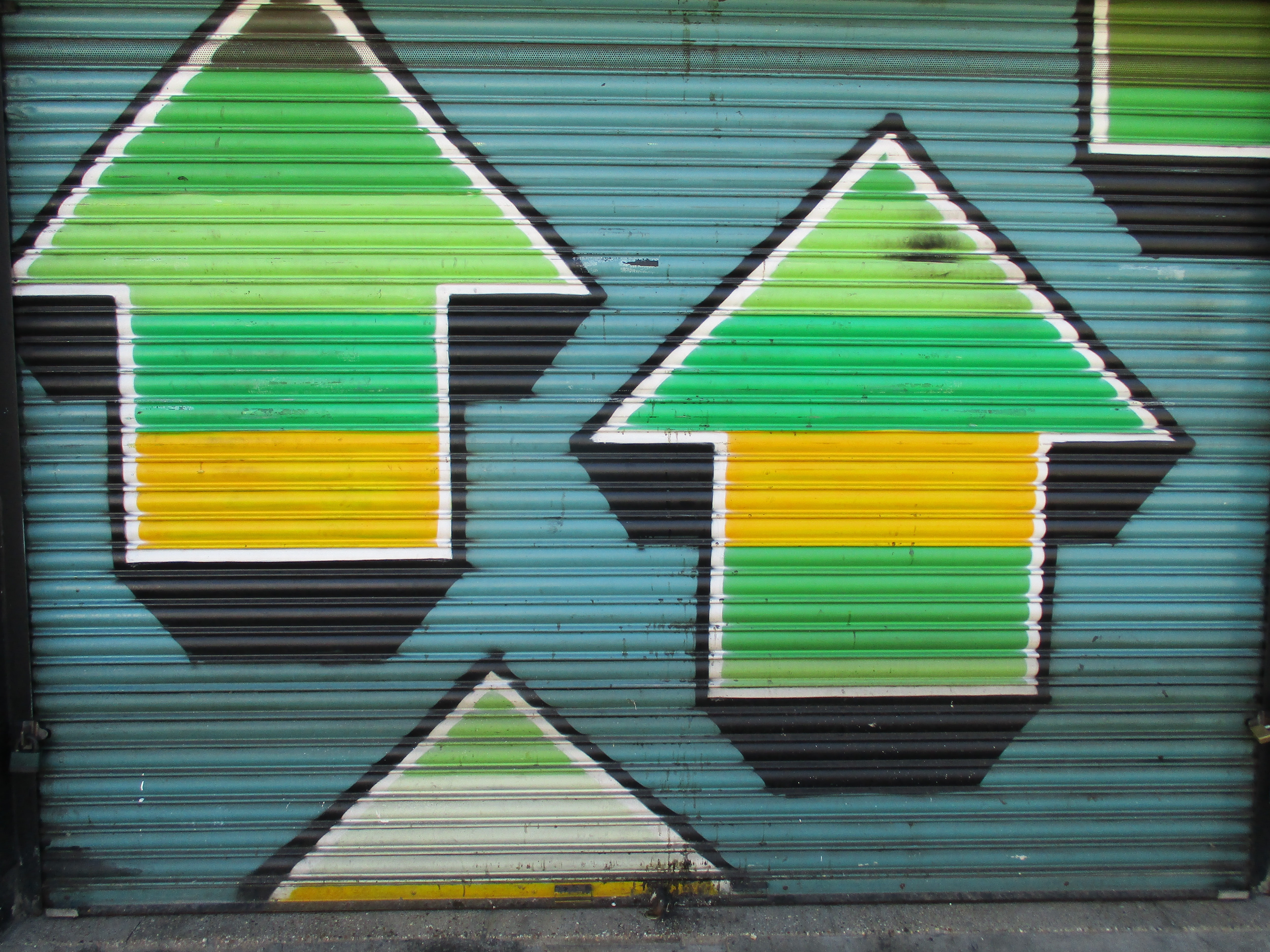 green, yellow, and black arrow up painted wall