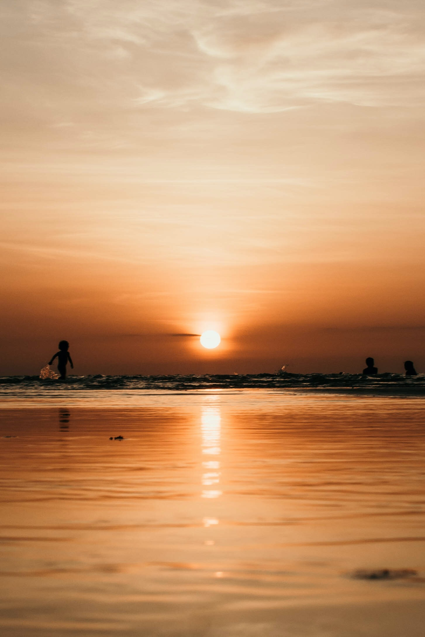 silhouette photography of two person on body of water during sunset