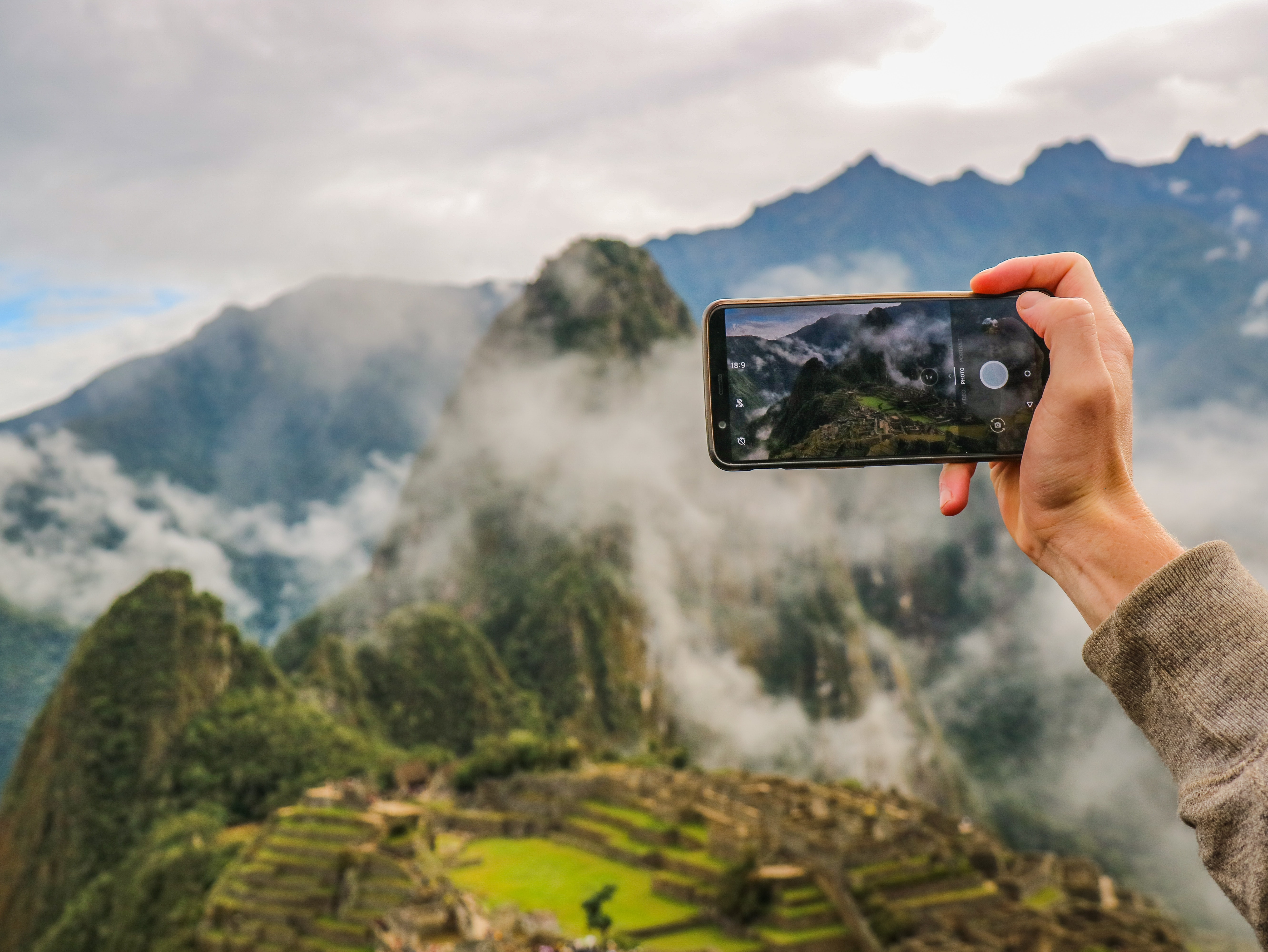 person holding smartphone taking picture of green mountain