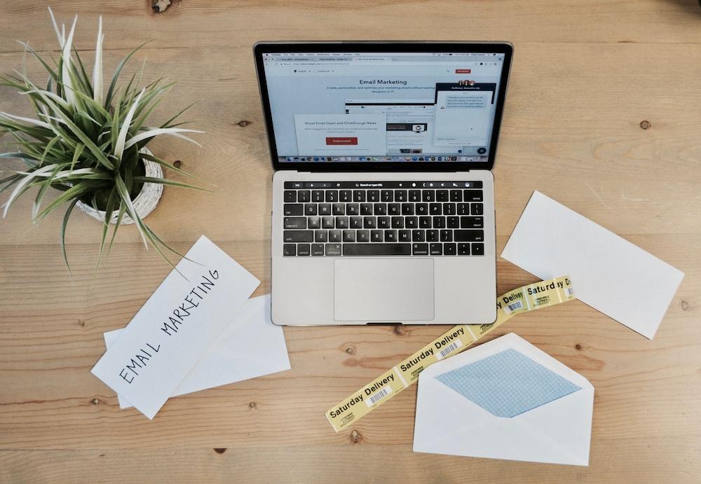 ホワイトペーパーと植物の横にあるMacBook Pro