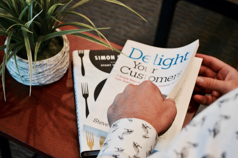 person holding Delight your Customer book