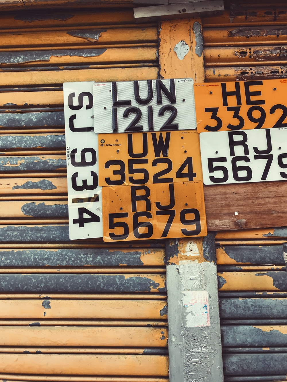 assorted license plates hanging on roller shutter