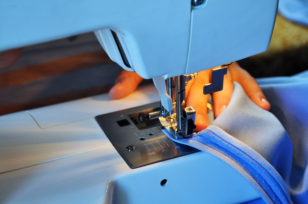 person sewing using sewing machine